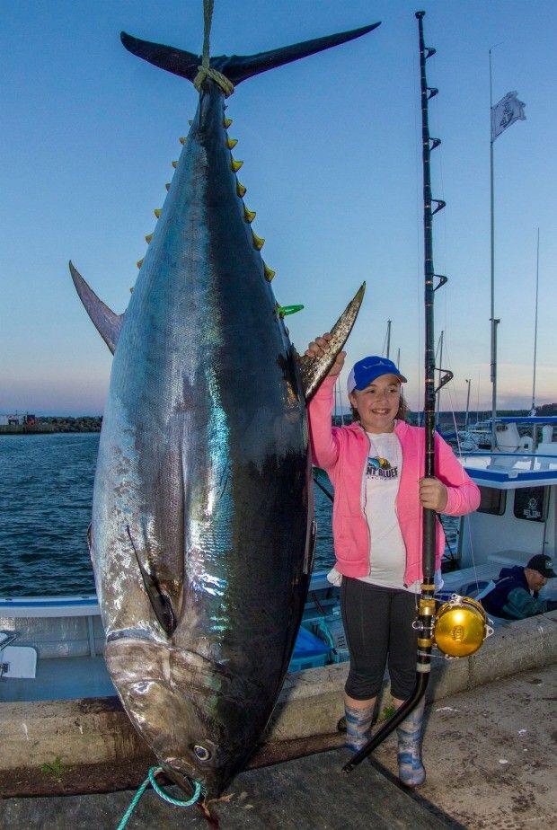 A pequena Jenna com o atum: menina pesa 225 kg a menos que o peixe gigante (Foto: The Grosby Group)