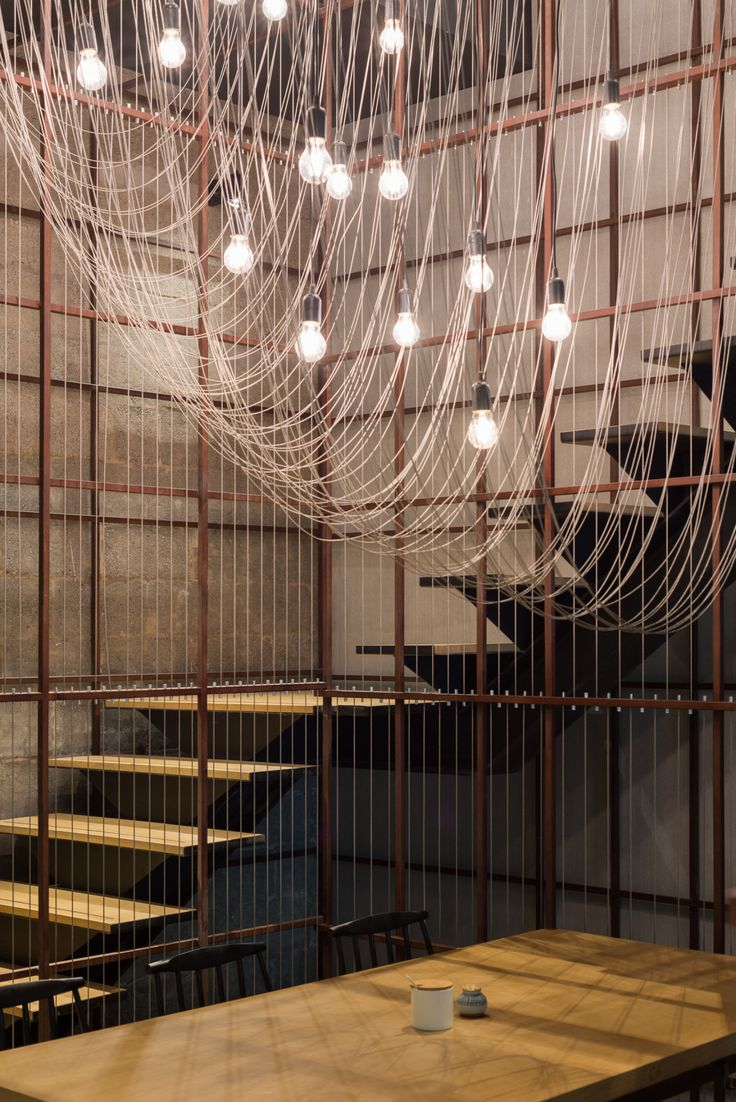 """Based on the original """"noodle rack"""" concept, Lukstudio has created a layered experience at the Longxiaobao flagship restaurant in Beijing where dining areas are shaped by multiple steel frames and wires."""