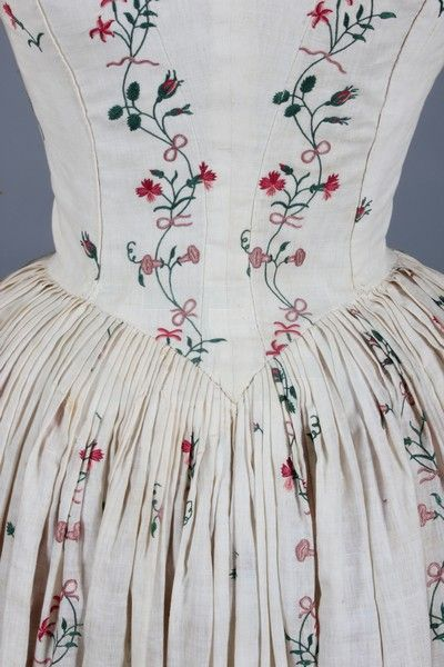 Detail back view robe à l'Anglaise, circa 1770-80. White cotton embroidered in chain stitch with stripes and sprigs of pinks, convolvulus, dog roses, honeysuckle, tied with pink bows, closed-front bodice panels with drawstring to neck, the sleeves with shaped elbows adorned with ruffles.
