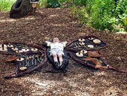 "A child-sized butterfly frame on the ground . Children decorate the wings with items from a bin of loose parts (pinecones, tree slices, leaves, etc.) and then can lie down on the body to ""become"" their butterfly."
