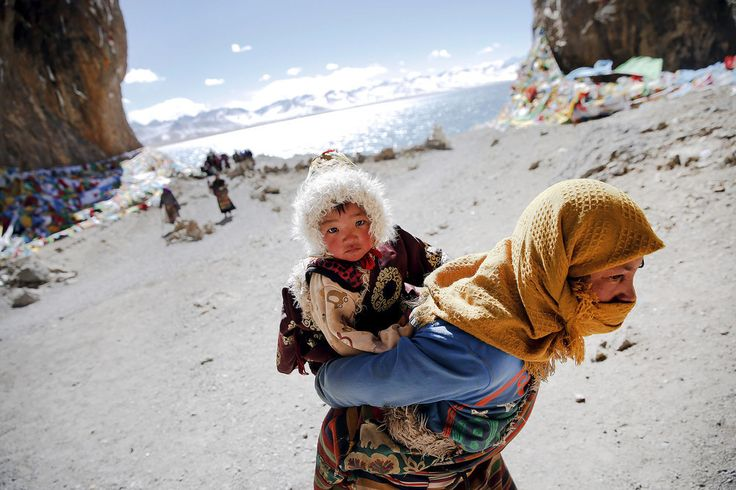 A #Tibetan woman carries a child as they visit #Namtsolake in the #Tibet Autonomous Region, #China. Located four hours' drive from #Lhasa at an altitude of around 15, 479 ft above sea level, #Namtso lake is not only the highest #saltwaterlake in the world but also considered #sacred, attracting throngs of #devotees and #pilgrims.