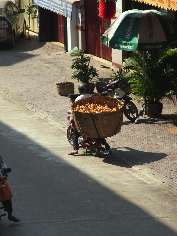 The rider is delivering freshly baked baguettes to local restaurants throughout the city. They are transported in a large wicker basket which is strapped to the motorcycle seat. There is barely enough room for the rider to sit, so he has to adopt a position similar to that of a ski jumper - straight posture and leaning forward. His legs are spread, enabling him to balance the load.    The price of a plain baguette is 800-1000 riels (25 cents / 15 pence)    Website: www.tropicalasiatravel.com