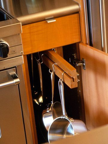 Vertical Space Solutions  Hang On  If you don't have a spot for a wall- or ceiling-mount pot rack, recast one or two base cabinets flanking the range. This narrow compartment is just wide enough for favorite pots and pans, which hang from