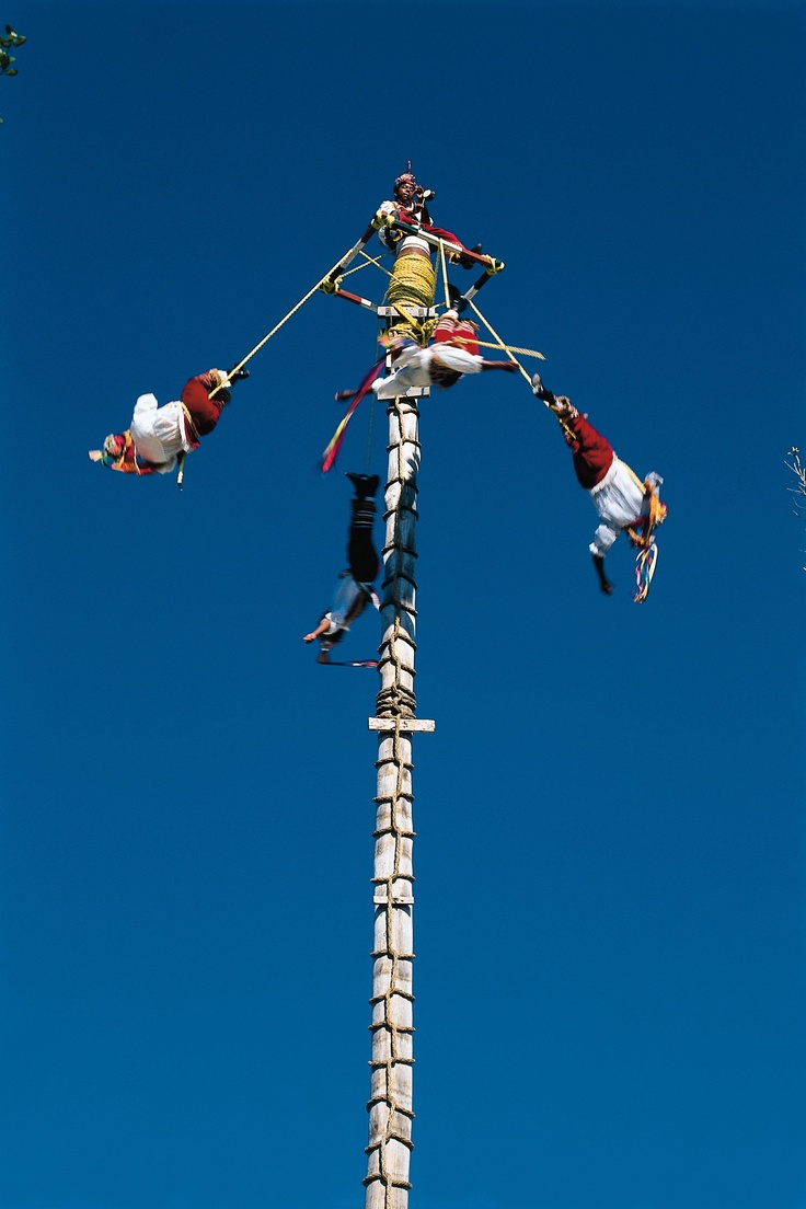 Papantla's Flying Men, Xcaret. Mexico The Flying men known in Mexico as the Voladores de Papantla can be seen above the clear blue sky of Xcaret in Cancun Mexico. They are native from Totonacapan, a region located in the coastline of the Mexican state of Veracruz and in Sierra Norte of Puebla. Be amazed with this show in Xcaret and learn more about one of the most unique traditions in Mexico with a culture tour in Cancun to Xcaret eco theme park.