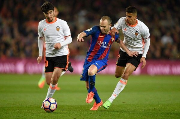 Barcelona's midfielder Andres Iniesta vies with Valencia's Portuguese defender Joao Cancelo (R) and Valencia's Argentinian midfielder Enzo Perez (L)  during the Spanish league football match FC Barcelona vs Valencia CF at the Camp Nou stadium in Barcelona on March 19, 2017. / AFP PHOTO / LLUIS GENE