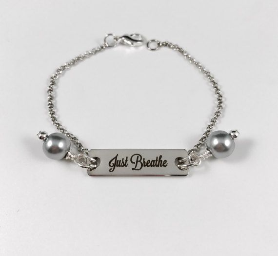 Just Breathe  This beautiful bracelet is made with a laser engraved stainless steel tag. Adorned with two wire wrapped pearl drops. You may choose the color pearls you would like (options shown in 5th photo). These bracelets are made from high-quality stainless steel and hand