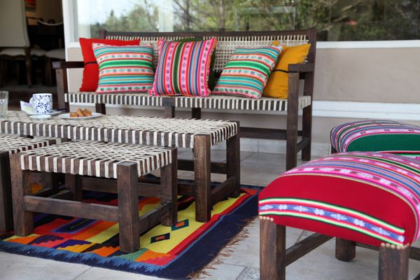 Sillón de tres cuerpos con almohadones de Aguayo , banquetas con tiento , banquetas tapizadas y tapiz de alpaca
