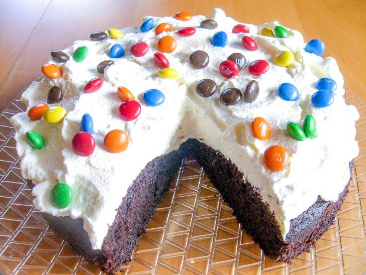 Bakelyst.no: Her har du en feststemt, amerikansk sjokoladekake! Den bløte sjokoladekaken har Browniesaktig konsistens, hvilket er deilig sammen med kremen på toppen. M&M's til pynt gjør kaken fargerik og fin! Det går like bra å bruke Smarties eller norske Nonstop.