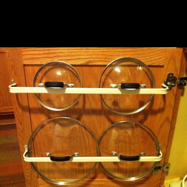 Rack for pot lids made by installing cheap curtain rods to the inside of lower cabinet doors.