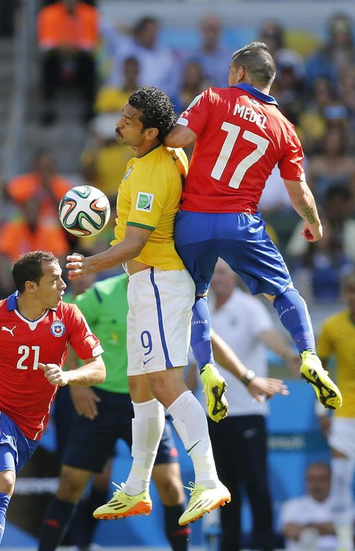 Chile's Gary Medel, right, and Brazil's Fred, go for a header during the World Cup round of 16 soccer match between Brazil and Chile at the Mineirao Stadium in Belo Horizonte, Brazil, Saturday, June 28, 2014.