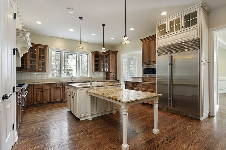 Kitchen with natural wood cabinets and white island.  Island has dine-in extension down the center of the kitchen