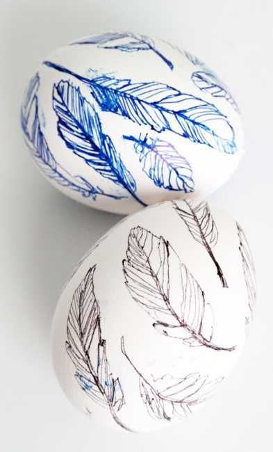 blue and black marker drawings on white easter eggs