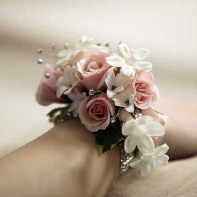 Wrist Corsage -- The FTD® Pure Grace™ Wrist Corsage is the perfect accent piece for any of the ladies in your wedding party. Pink spray roses, white hyacinth, stephanotis and variegated ivy vines are cleverly arranged to create a fantastic look. Accented by rhinestone spray pics and secured by a sparkling flower bracelet, this corsage exudes charm and feminine beauty.