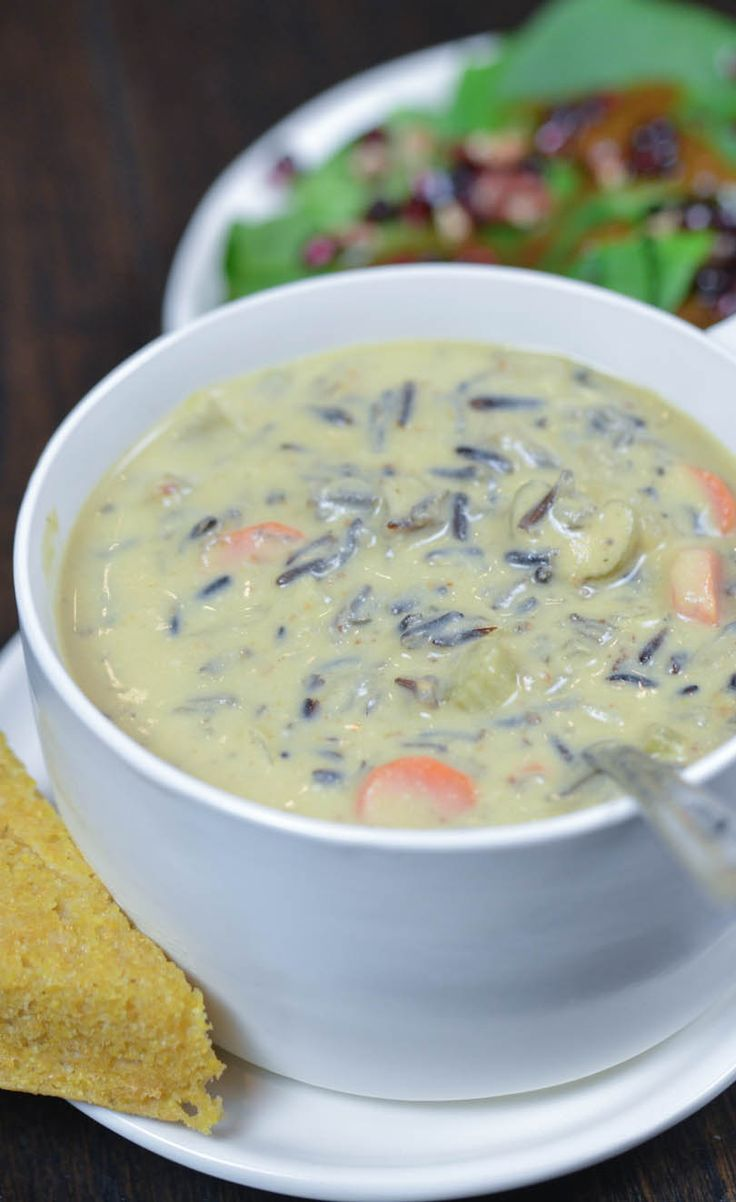 Vegan, chunky, creamy wild rice soup steaming hot served with corn bread and salad.