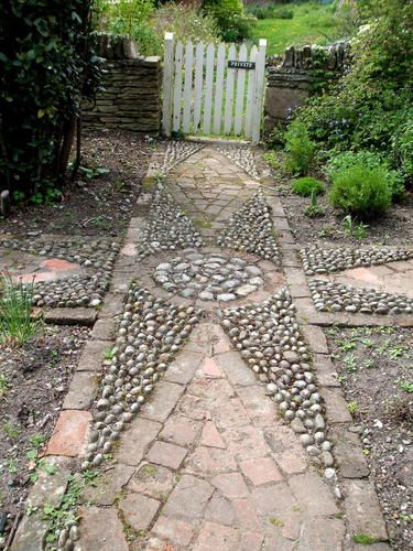gate at the end of an old garden path... nice mosaic rock art. ID LIKE THIS LEADING OUT TO MY LITTLE PIECE OF FOREST,  WONDER. IF I COULD DO THIS?