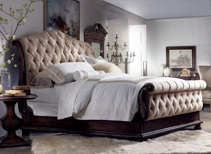 Traditional button tufting, brass nailhead trim,upholstered sleigh bed with lightly distressed rustic walnut finish.