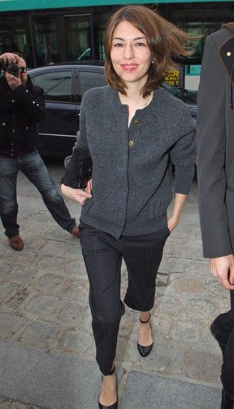 Sophia Coppola in a grey cardigan  black tailored trousers