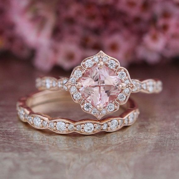 This stunningly unique wedding ring bridal set features a vintage floral engagement ring with a 6x6mm cushion cut conflict free cultured champagne peach sapphire set in a solid 14k rose gold floral setting. To complete the gorgeous look, matching scalloped diamond wedding band is created