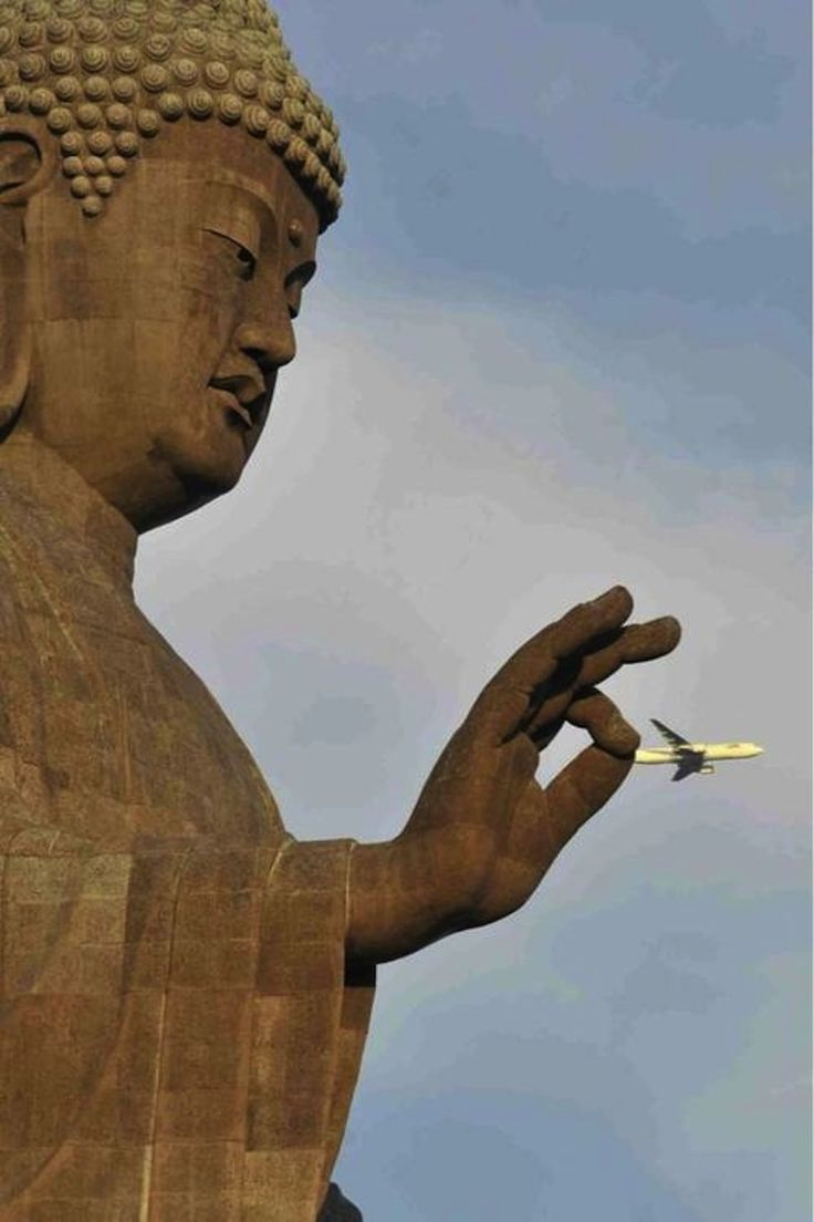 A statue of Buddha captures a commercial airliner by its tail.