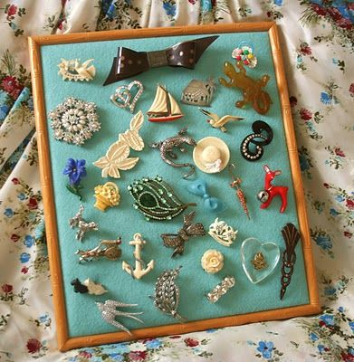 How to make a framed brooch board. They use felt... I wonder if you could cover felt with scarf?