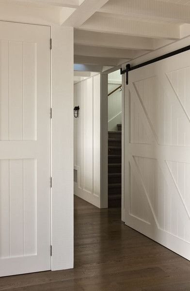 Farmhouse Hallway White Barn Doors And Dark Wood Floors