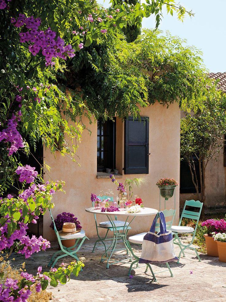Terraza del porche  Mesas y sillas de hierro verde agua marina, similares en Antic Centre. En la silla, bolso de lino azul y blanco de Aquit...:
