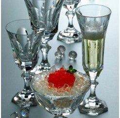 Cristalería de 48 piezas en cristal de Sèvres fabricada a mano con talla facetada compuesta por: 12 copas de agua, 12 copas de vino tinto, 12 copas de vino blanco y 12 copas de champagne. Se dice de Sèvres que es el cristal más transparente que jamás ha existido y es que no conviene olvidar que esta firma surge en 1750 para satisfacer directamente al Rey Luis XV de Francia.