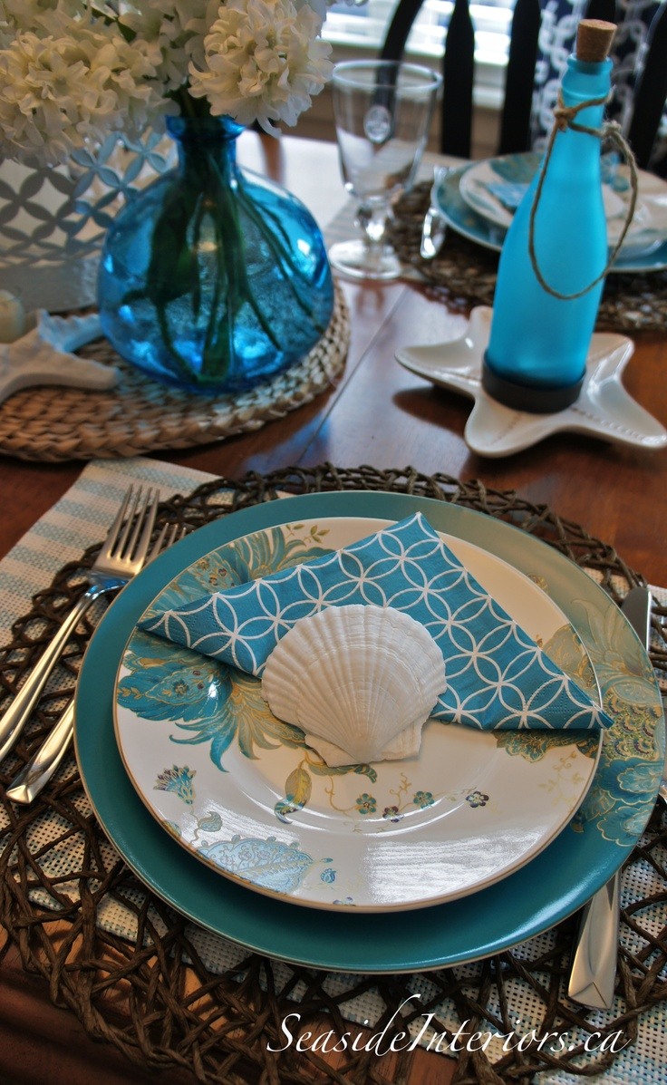 A lovely seaside inspired table setting that actually has little ocean elements, just a shell and a couple of starfish shapes.  The turquoise color, however, speaks of the sea.  Straw placements combined with lovely, elegant plates makes a perfect seaside look.