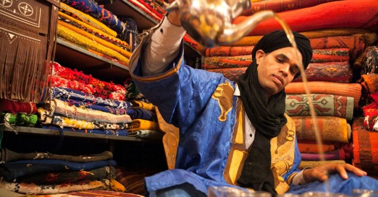 Um homem numa aldeia berbere, vestido com roupas tradicionais, enche copos de chá numa loja marroquina de tapetes. O chá berbere é embalado com ervas frescas e oferecido em sinal de hospitalidade