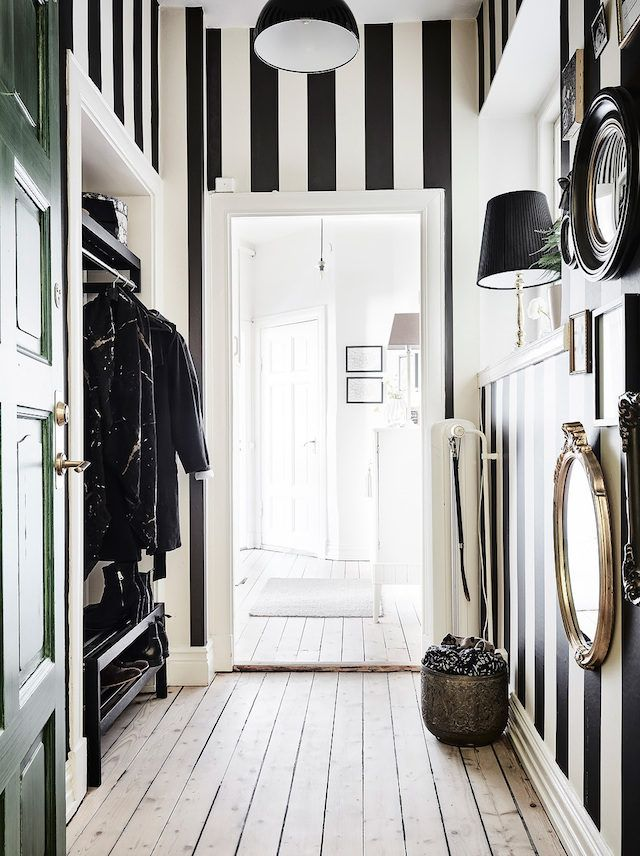 Black and white striped wallpaper and green door in the hall. Entrance.