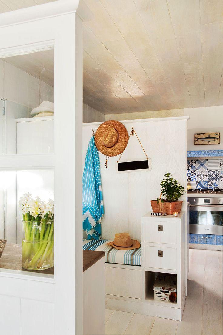 Recibidor con banco y mueble con cajones en blanco separado de la cocina por un murete que no llega al techo