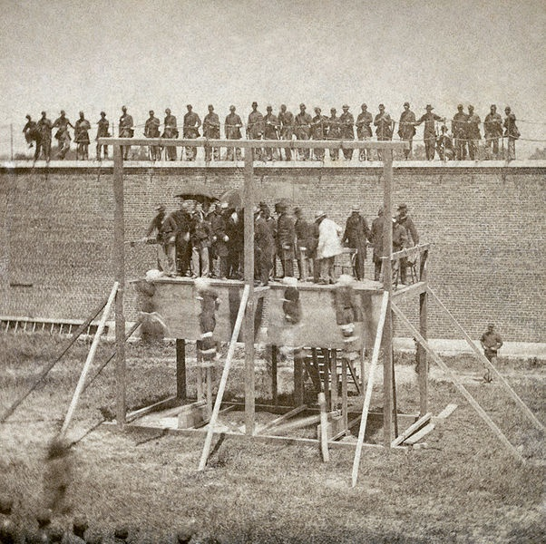 """Execution of Mary Surratt, Lewis Powell, David Herold, and George Atzerodt, conspirators of Abraham Lincoln assassination, on July 7, 1865 at Fort McNair in Washington, D.C.  photographic print on stereo card: albumen, stereograph. Original captions: """"Execution of the conspirators -- the drop""""; from reverse side of submission notes: """"The trap is sprung"""". en.wikipedia.org/..."""