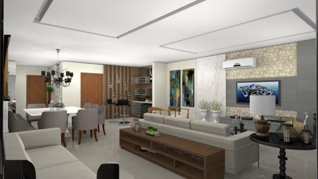 Em apartamento de alto padrão, ampla sala de 62 m², com quatro ambientes integrados, no Edifício Auguste Rodin. A divisão entre eles é feita com mobiliário, detalhamento do gesso e colocação do lustre. Sala de estar, tv, jantar e um hall de entrada charmoso com painel de madeira e adega.