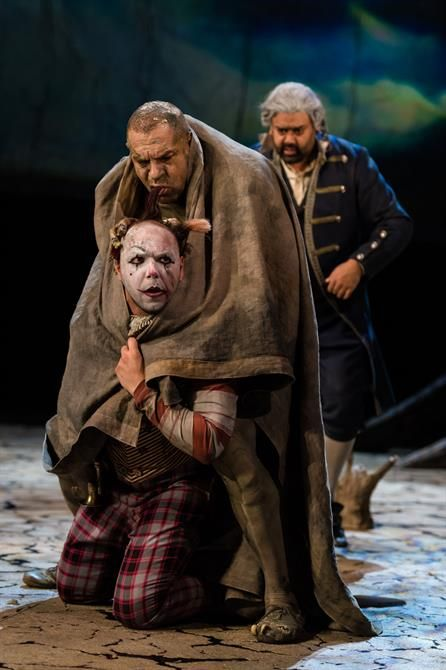 Trinculo and Caliban covered in a blanket while Stephano looks on - The Tempest RSC Stratford upon Avon