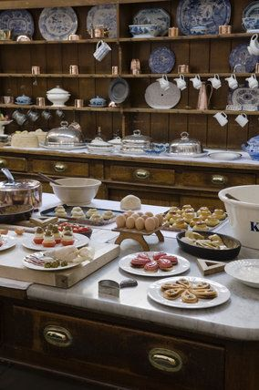 Table in the Kitchen laden with utensils and pastries with the dresser behind at Lanhydrock, Cornwall