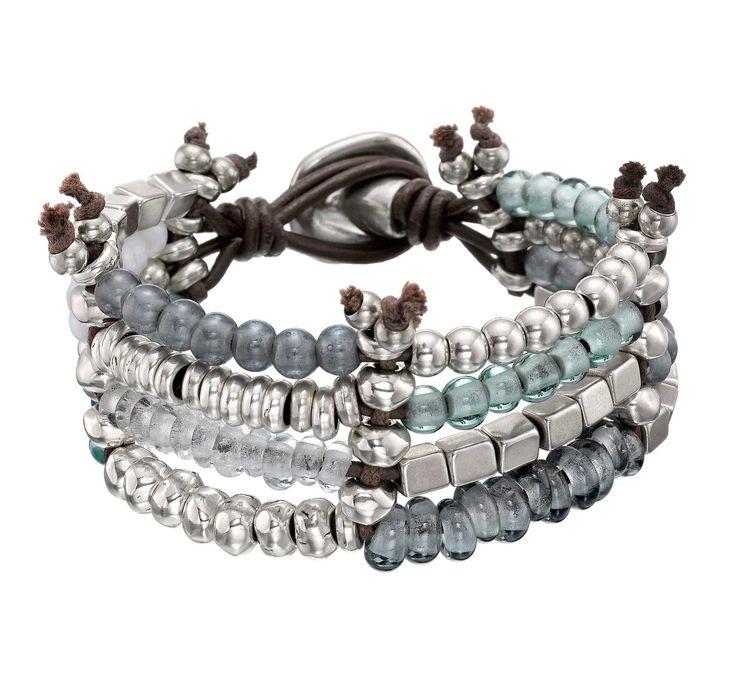 Pulsera de cuentas bañadas en plata combinadas con cristales en tonalidades azules y cordones de cuero marrón. Elaborado de manera artesanal en España.
