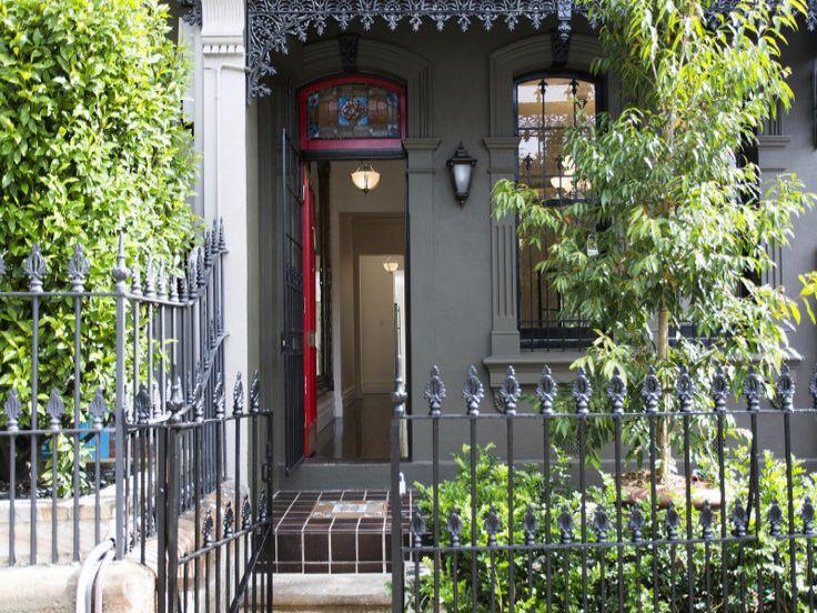 Перед домом находится небольшой палисадник огороженный забором. Окна и двери украшают красивые кованые решетки. Входная дверь также украшена витражом, что характерно для викторианских домов.  (викторианский,архитектура,дизайн,экстерьер,интерьер,дизайн интерьера,мебель,вход,прихожая) .