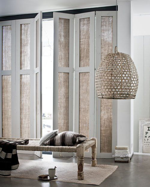 love these accordion levered fabric panels for window covering - the wicker lamp is also beautiful!