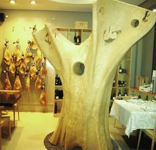 Decoración luminosa en tonos blancos y madera con una escultura impresionante de un árbol y jamones colgando; aire moderno, sencillo y acogedor. FUENTE: MISS MARIDAJES > Facebook https://www.facebook.com/Mismaridajes - Twitter https://twitter.com/mismaridajes - Web http://mismaridajes.blogspot.com.es/