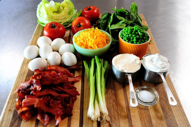 7 Layer Salad by Ree Drummond / The Pioneer Woman. A variation on:  - 1 head iceberg lettuce torn into small pieces  - 2 stalks celery - chopped  - 2 green onions - chopped  - 1 small bag frozen peas, add while still frozen  - 1/2 lb bacon browned and crumbled  - 1 and 1/2 cup cooked, chopped chicken (grilled)  - 1 cup grated cheese  - Aldi Garlic Vinaigrette