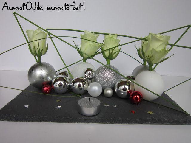 Centre de table réalisé avec de l'ardoise, des boules de Noël et des fleurs.