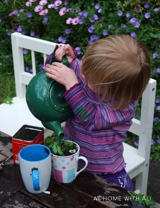 Pouring and mixing water, tea and flowers together in an outdoor kid cafe. Mud kitchen addition?