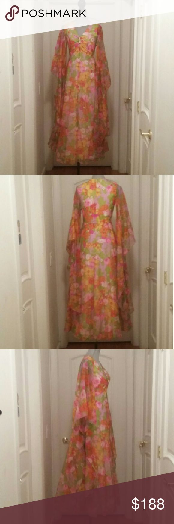 """Spectacular VTG Chiffon Evening Gown with Tags Reminds me of a gown Elizabeth Taylor would have worn Vintage 1950's or 60's Stunning Floral Chiffon Dress with Sheer Angel Sleeves V Neckline with 2.5"""" x  3/4"""" gold metal brooch embellishment with rainbow colored rhinestones 3 are missing which can easily be replaced. .price reflects flaw Rayon lining, Nylon Union Label & Original Department store Tags Measurements flat one sided  Shoulders  Chest:18"""" Waist: 14.5"""" Length: 56"""" Vintage Dresses"""