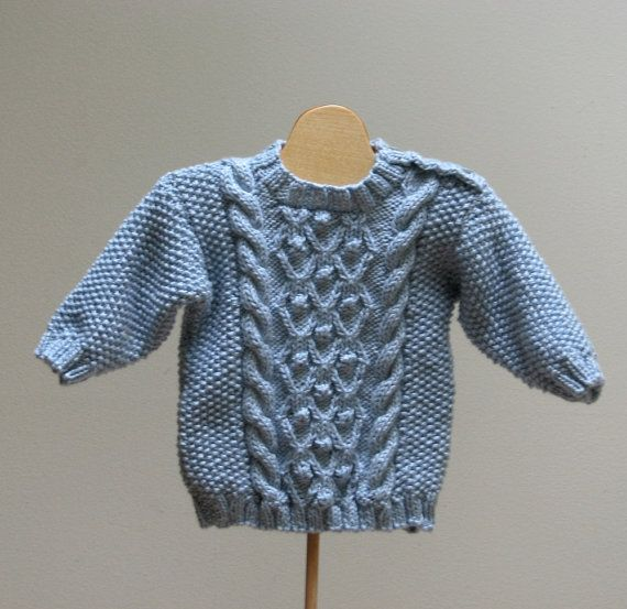 This miniature version of an Aran sweater would make a wonderful outfit for a baby boy.  This size ready to ship. Email me for other colors and sizes.  It is a soft baby blue color and made from a cotton blend yarn which washes well does not stretch out like 100% cotton tends to do.  There are cables back and front and it has buttons on one shoulder for easier dressing.