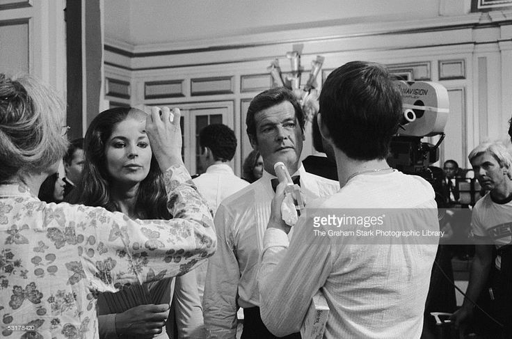 British actors Barbara Kellerman and Roger Moore being cooled by crew members with small electric fans on the set of 'The Sea Wolves' 1980.