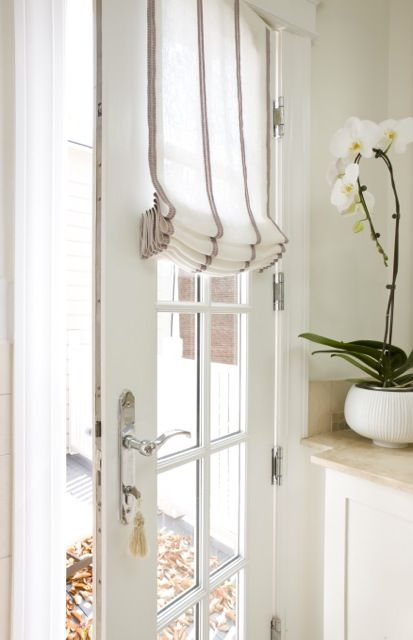 Sally Steponkus Interiors: Mudroom door with glass panes covered in French vintage grain sack fabric roman shade.