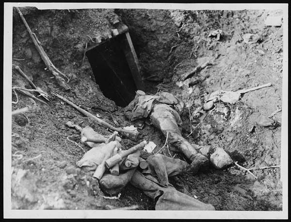Dead German outside dug-out    Dead German soldier, near Arras, France, during World War I. A dead German soldier lying outside the entrance to a dugout. Abandoned rifles and stick grenades lie in the trench beside him. This photograph was probably taken in the later part of the war, as in the earlier years the stick grenades had rounded ends to the handles. It may refer to the Arras campaign of April 1917.    In April 1917, the Allies launched a vicious and initially very successful attack on the Germans in the area around Arras. Their gains against the enemy defences were, however, not consolidated and the Germans counter-attacked.: Photo Shared, Wwi Photo