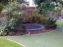 Sunken trampoline in landscaping, surrounded by mulch. Mulch is supposed to be a safer landing surface, since it has more give than grass on dirt in case the kids over-jump. It also blends into the garden area better.