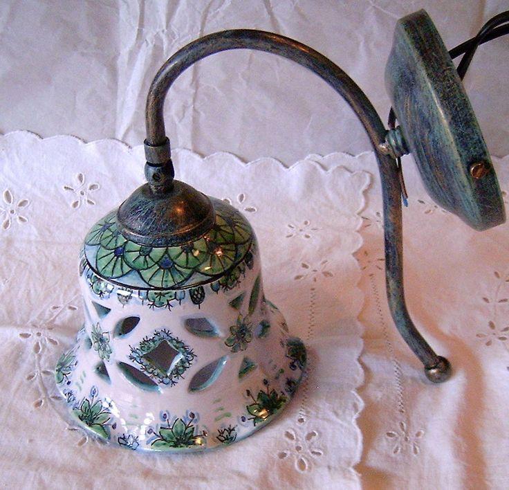 Applique-Lume campanella in maiolica con braccetto in metallo brunito.