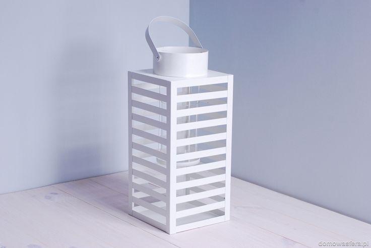 Metalowy lampion w minimalistycznym stylu. W pięknym białym kolorze, wykonany na wzór latarni morskiej. Posiada szklany wkład w formie walca, mającego na celu osłonięcia ognia świeczki przed wiatrem. Szklany wkład jak i koszyk na świeczkę można łatwo wyjąć przez komin latarni.